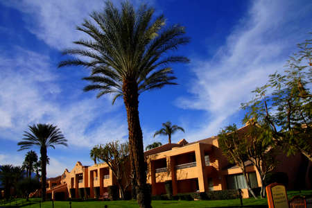 a mirage: RANCHO MIRAGE, CALIFORNIA - DEC 20, 2014 - Southwestern style hotel buildings in green oasis with Palm trees,  Rancho Mirage, California