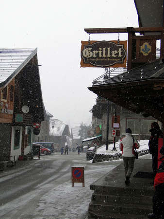 come in: CHATEL, FRANCE - MAR 3, 2010 -Skiers come back to town in a snowstorm  in Chatel, France.