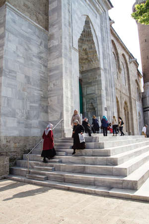 camii: BURSA, TURKEY - MAY 22, 2014 - Women with scarves leave the Ulu Camii mosque just before afternoon prayers Bursa, Turkey