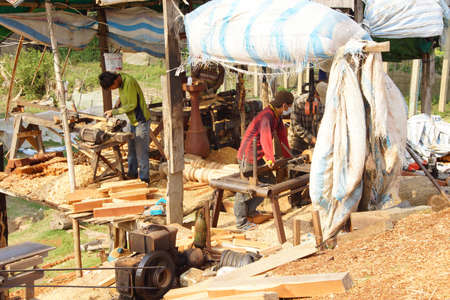 KRATIE, CAMBODIA - FEB 9, 2015 - Worker shaping timber for balustrade,  Kratie Province,  Cambodia