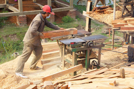 shaping: KRATIE, CAMBODIA - FEB 9, 2015 - Worker shaping timber for balustrade,  Kratie Province,  Cambodia