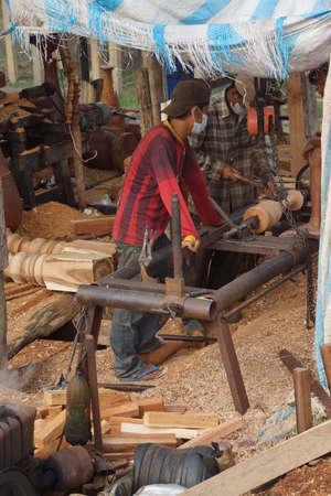 balustrade: KRATIE, CAMBODIA - FEB 9, 2015 - Worker shaping timber for balustrade,  Kratie Province,  Cambodia