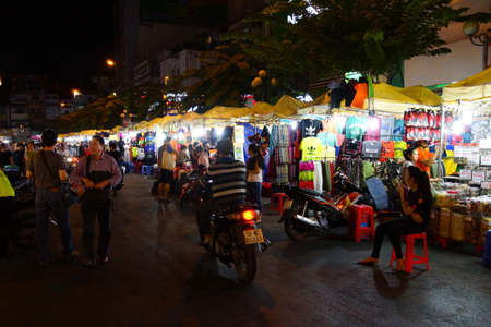 mingle: SAIGON - FEB 5, 2015 - Motorbikes mingle with pedestrians in the night market, Saigon (Ho Chi Minh City). Vietnam