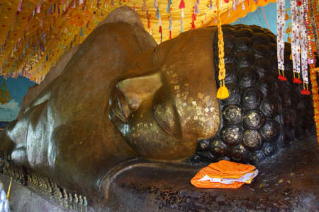 Huge reclining Buddha statue with flakes of gold leaf placed by pilgrims,  Phnom Kulen, Cambodia