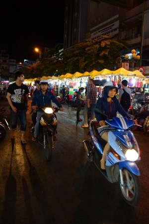 mingle: SAIGON - FEB 5, 2015 - Motorbikes mingle with pedestrians in the night market, Saigon (Ho Chi Minh City). Vietnam