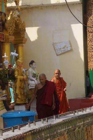 YANGON, BIRMA - 18 februari 2015 - Boeddhistische monniken een bezoek aan een planetaire post van de Shwedagon Pagoda, Yangon (Rangoon), Myanmar (Birma)