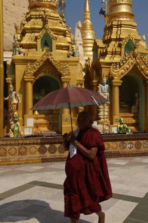 YANGON, BIRMA - 18 februari 2015 - Boeddhistische monnik met paraplu, Shwedagon Pagoda, Yangon (Rangoon), Myanmar (Birma)