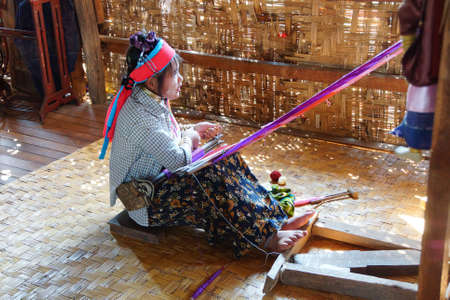 necked: INLE LAKE, MYANMAR - FEB 28, 2015 - Long necked Kayan Padaung woman weaving on a loom,  Inle Lake,  Myanmar (Burma)