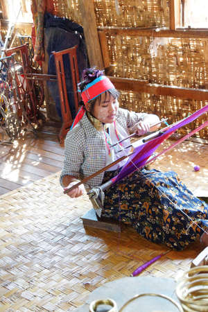 INLE LAKE, MYANMAR - FEB 28, 2015 - Long necked Kayan Padaung woman weaving on a loom,  Inle Lake,  Myanmar (Burma)