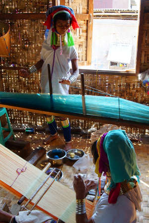 long lake: INLE LAKE, MYANMAR - FEB 28, 2015 - Long necked Kayan Padaung woman weaving on a loom,  Inle Lake,  Myanmar (Burma)