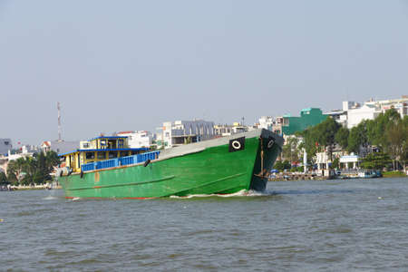 cai rang: Large green cargo boat outbound from the floating market, Cai Rang,  Vietnam Stock Photo