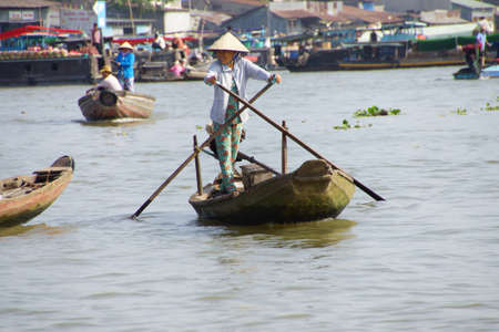 outbound: CAI RANG, VIETNAM - FEB 7, 2015 - Woman standing and rowing her small boat in the floating market of  Cai Rang,  Vietnam
