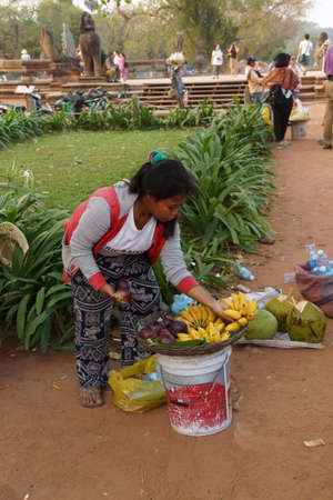 ANGKOR WAT, CAMBODIA - FEB 13, 2015 - Young Cambodian woman sells fruit outside  Angkor Wat,  Cambodia