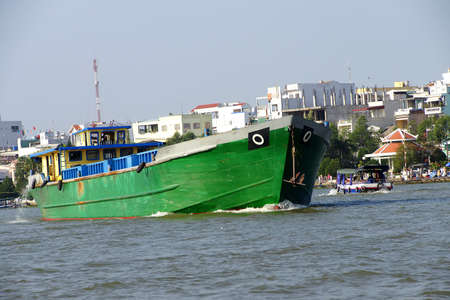 cai: Large green cargo boat outbound from the floating market, Cai Rang,  Vietnam Editorial