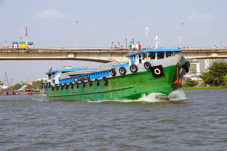 cai rang: Large green cargo boat outbound from the floating market, Cai Rang,  Vietnam Editorial