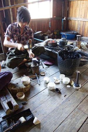 heats: INLE LAKE, MYANMAR - FEB 28, 2015 - Young silversmith heats silver over a fire, Inle Lake Myanmar (Burma)