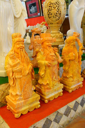 philosophers: Yellow statues of laughing Confucian philosophers,  Crafts factory, Northern Vietnam Stock Photo