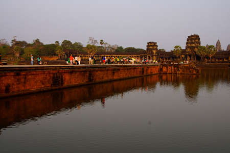 moat: ANGKOR WAT, CAMBODIA - FEB 13, 2015 - Sunset, tourists on the causeway across the moat of Angkor Wat,  Cambodia