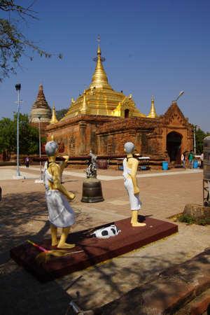 Standbeelden, 2 monniken dragen grote bel, Bagan Myanmar (Birma)