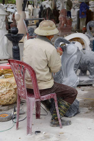 power tools: HAIPHONG, VIETNAM - FEB 1, 2015 - Artist carving a stone statue with power tools,  Crafts factory, Northern Vietnam