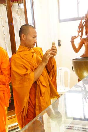 phnom penh: PHNOM PENH, CAMBODIA - FEB 8, 2015 - Young Buddhist monk checking his cellphone,  Phnom Penh,   Cambodia Editorial