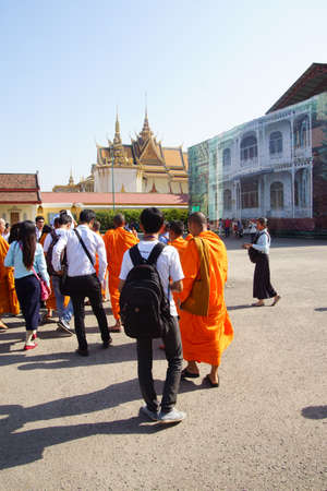 phnom penh: PHNOM PENH, CAMBODIA - FEB 8, 2015 - Young Buddhist monks and other young visitors explore the National Palace,  Phnom Penh,   Cambodia Editorial