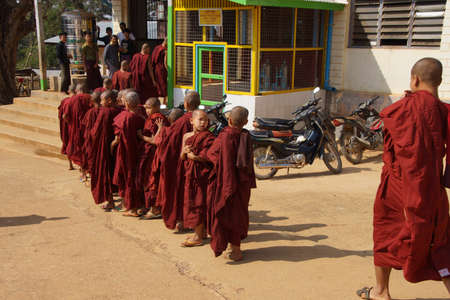 lining up: KYAUKME, MYANMAR - FEB 21, 2015 - Young Buddhist students lining up before going in for the main meal of the day, Kyaukme Myanmar (Burma)