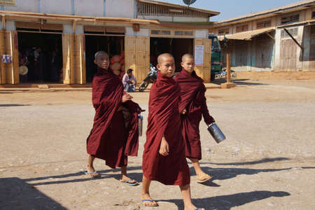 buddism: AUNG BAN, BURMA - FEB 28, 2015 - Three young monks looking for food at the weekly market,  Aung Ban,  Myanmar (Burma)