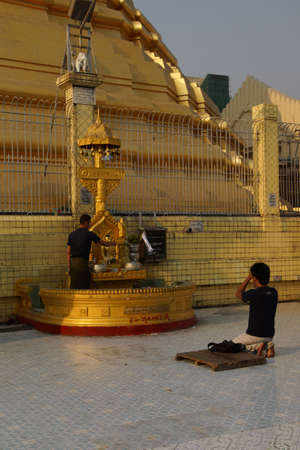 planetary: YANGON, MYANMAR - MAR 2, 2015 - Buddhists pray at the planetary post of their birth day,  Botataung Pagoda, Yangon,  Myanmar (Burma)
