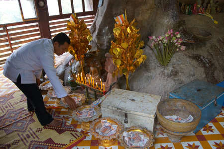 PHNOM KULEN, CAMBODIA - FEB 15, 2015 - Worshippers leave donations at altar of the reclining Buddha,  Phnom Kulen, Cambodia Sajtókép