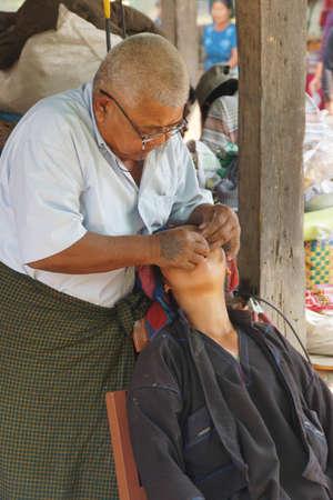 INLE LAKE, MYANMAR - MAR 1, 2015 - Dentist treats a patient at the weekly market, Inle Lake Myanmar (Burma)