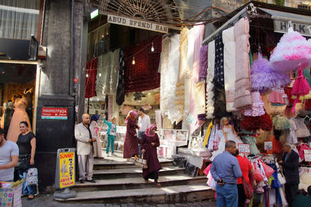 grand child: ISTANBUL, TURKEY - MAY 17, 2014 -Locals shop for childrens clothes in the narrow streets near the Egyptian Bazaar,  in Istanbul, Turkey