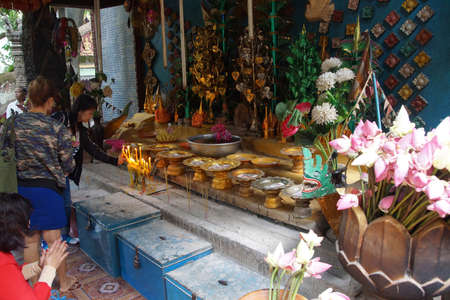 worshipper: PHNOM KULEN, CAMBODIA - FEB 15, 2015 - Worshippers leave donations at altar of the reclining Buddha,  Phnom Kulen, Cambodia Editorial