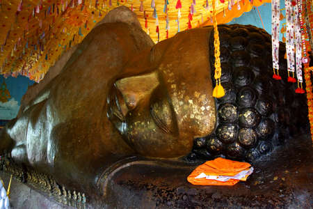 cambodia sculpture: Huge reclining Buddha statue with flakes of gold leaf placed by pilgrims,  Phnom Kulen, Cambodia