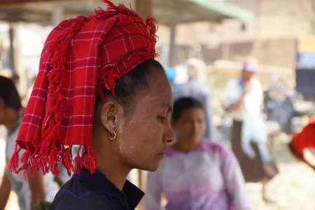 INLE LAKE, MYANMAR - MAR 1, 2015 - Woman wearing traditional Shan red headdress, at the weekly market near  Inle Lake,  Myanmar (Burma) Редакционное