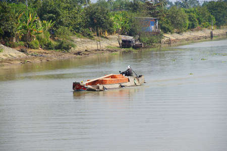 mekong: Small boat carries bricks across the Mekong River,  Vietnam