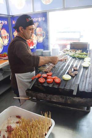 kabob: APHRODISIAS, TURKEY, - MAY 26, 2014 - Cook grilling sausages and kabob skewers for lunch in restaurant near  Aphrodisias,  Turkey