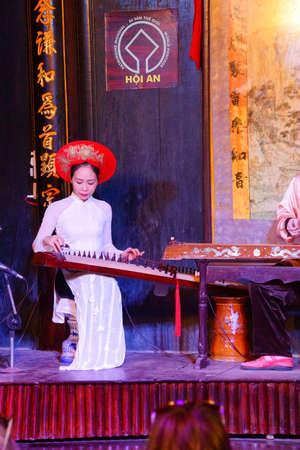 stringed: HOI AN, VIETNAM - FEB 3, 2015 - Woman plays ancient Chinese stringed instrument,  Hoi An, Vietnam Editorial