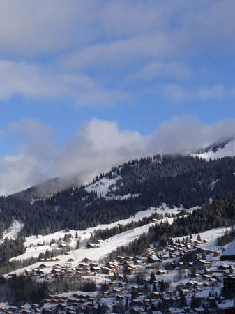 reaches: Early morning light reaches the wooden chalets of the alpine village of Chatel, France