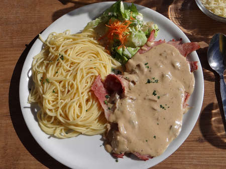 soleil: Ham with cream sauce and pasta and salad,  , served outdoors at an alpine restaurant, Portes du Soleil, France