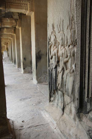 apsara: Apsara dancer statues carved into wall at head of long columned arcade gallery,  Angkor Wat,  Cambodia Stock Photo