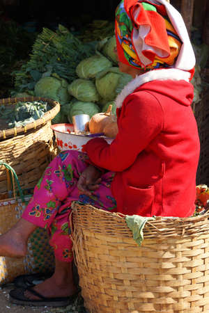 Shan woman tends a vegetable stand at the  weekly wholesale market,  Aung Ban,  Myanmar (Burma)