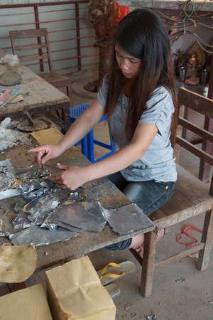combining: KYAUKME, MYANMAR - FEB 21, 2015 - Combining silver lead foil and bamboo paper, Kyaukme Myanmar (Burma)
