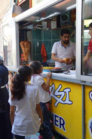 kabab: URFA, TURKEY - JUN 7, 2014 - Cook sells doner kebab shawarma from the spit from his small shop in Sanliurfa,  Turkey