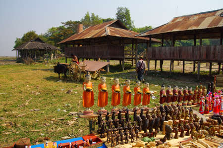 weekly market: Statues of nats in foreground as Young man drives his ox cart from the weekly market ,  Inle Lake,  Myanmar (Burma)