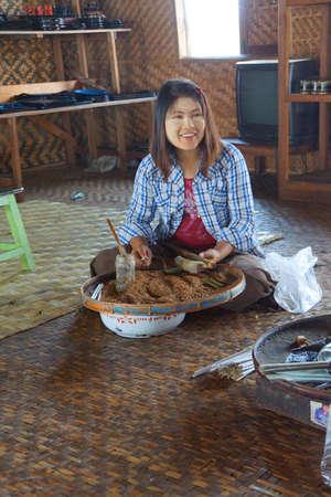 inle: INLE LAKE, MYANMAR - MAR 1, 2015 - Young girl rolling cheroot cigars,  Inle Lake,  Myanmar (Burma)