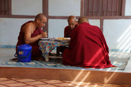 KYAUKME, MYANMAR - FEB 21, 2015 - Buddhist monks eating their main meal of the day at noon, Kyaukme Myanmar (Burma) 新聞圖片