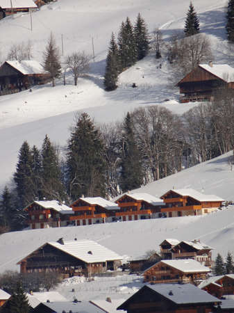 chalets: Early morning light reaches the wooden chalets of the alpine village of Chatel, France