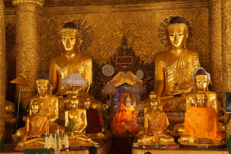 witness: Buddha statues in Bhumiparsa Mudra position, Calling the Earth To Witness the Truth, Shwedagon Pagoda Yangon (Rangoon),  Myanmar (Burma) Stock Photo