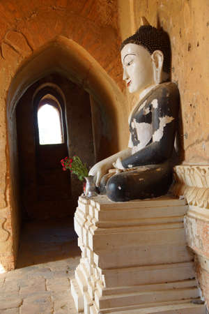 witness: White Buddha in black robe, in Bhumiparsa Mudra position, Calling the Earth To Witness the Truth, Dhammayangyi Temple, Bagan,  Myanmar (Burma)